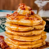 pile of Bacon Pancakes with syrup and bacon on top