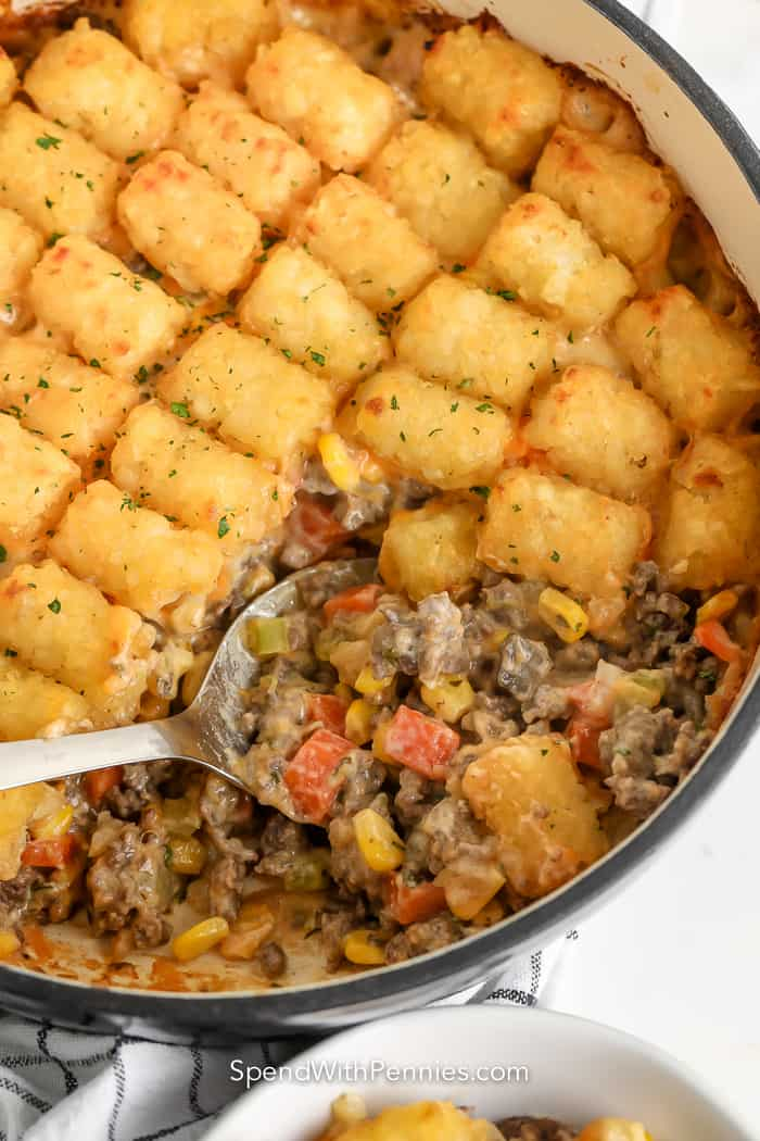 serving spoon scooping classic tater tot casserole