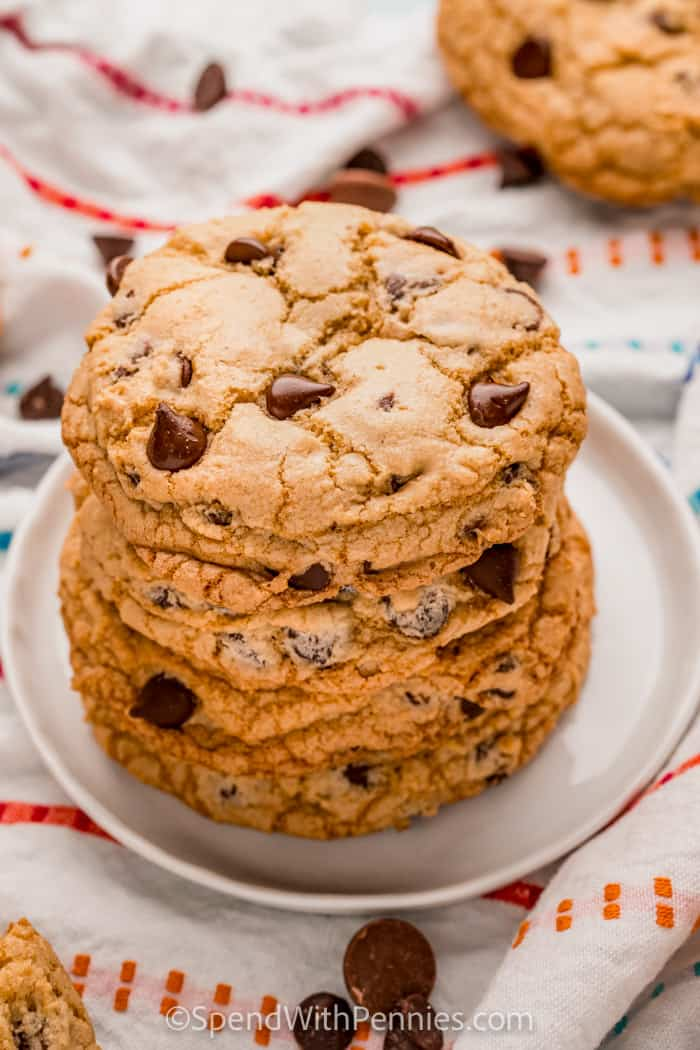 Chocolate Chip Cookies pile on a plate with chocolate chips around it