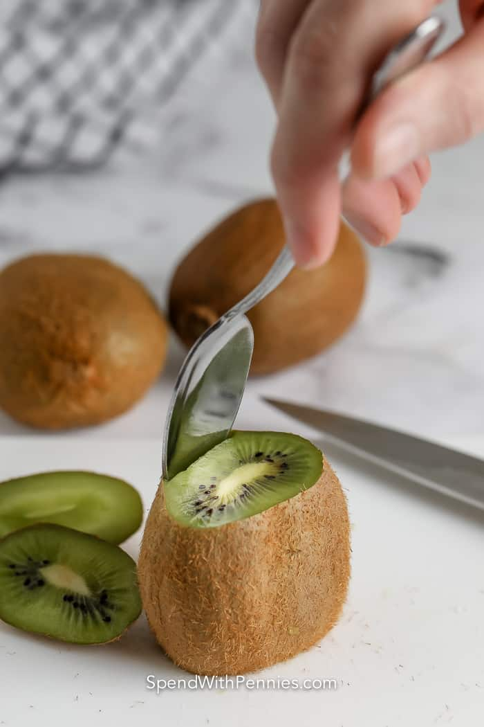 starting to peel skin off of a kiwi with a spoon