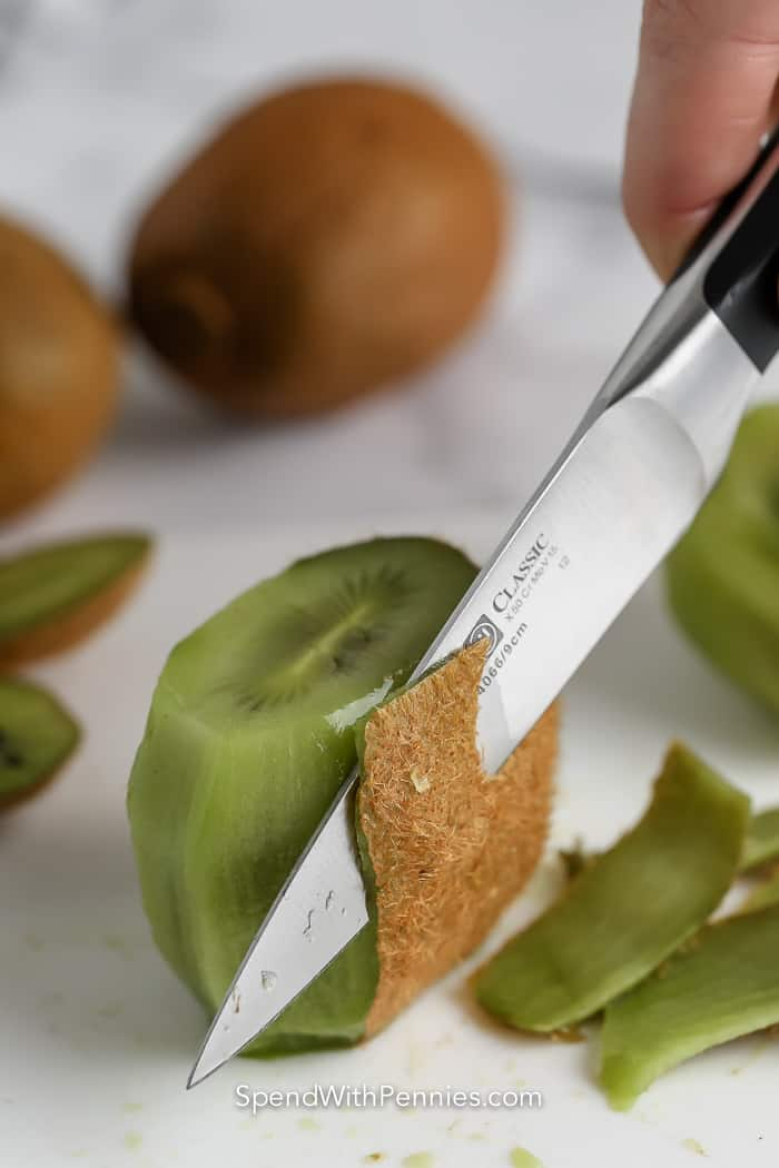 cutting skin off of a kiwi with a knife