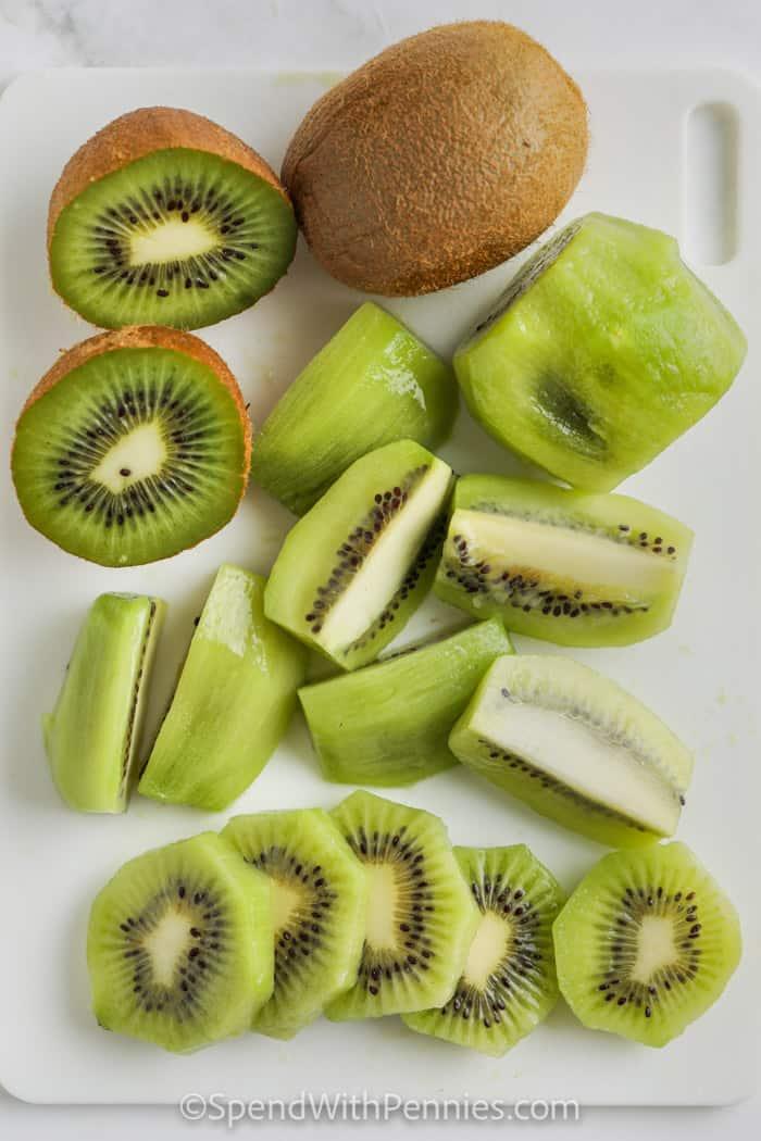 cut and sliced kiwi on a cutting board to show How to Cut Kiwi