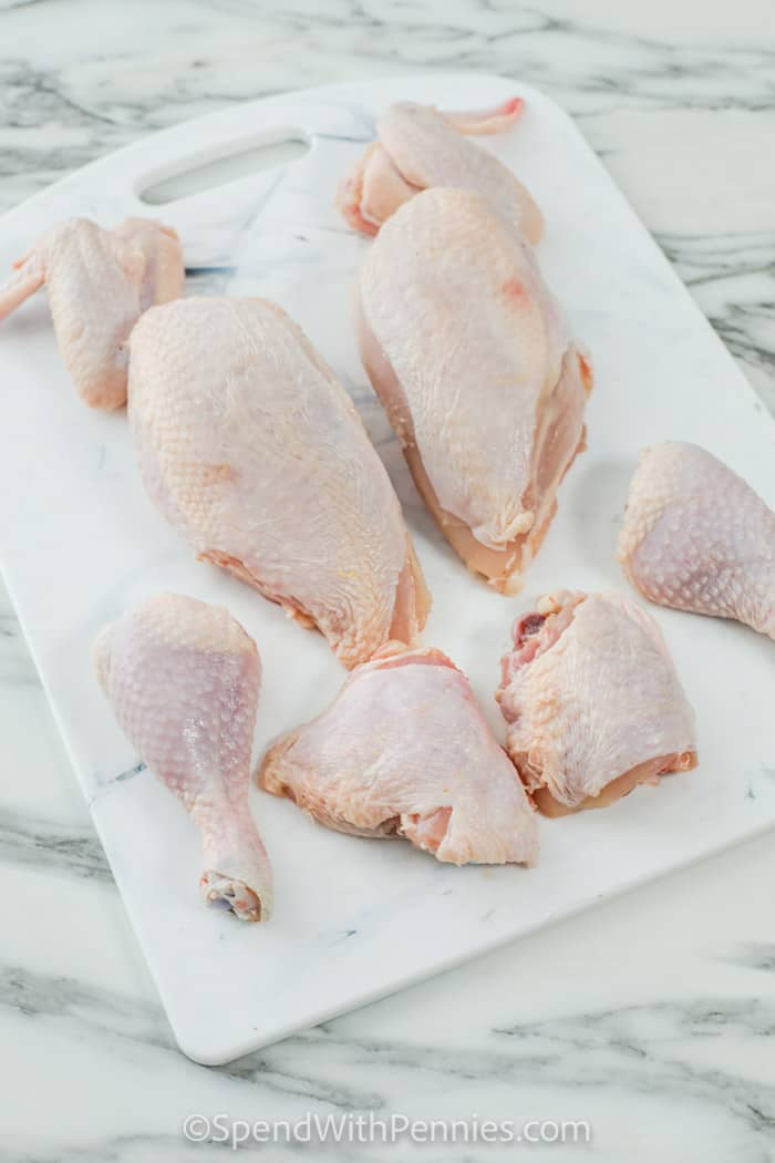 showing How to Cut a Whole Chicken with cut pieces on a cutting board