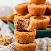 pile of Peanut Butter Cookies Cups with a bite taken out of one