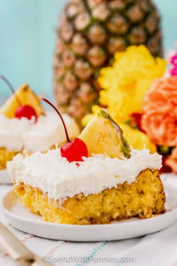 plated Pina Colada Cake with a cherry and pineapple on top