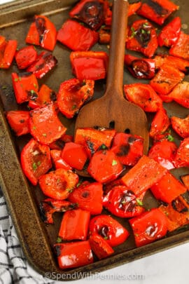 Roasted Red Peppers cooked on a baking sheet with a spoon
