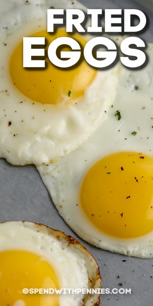 three fried eggs on a grey plate with text