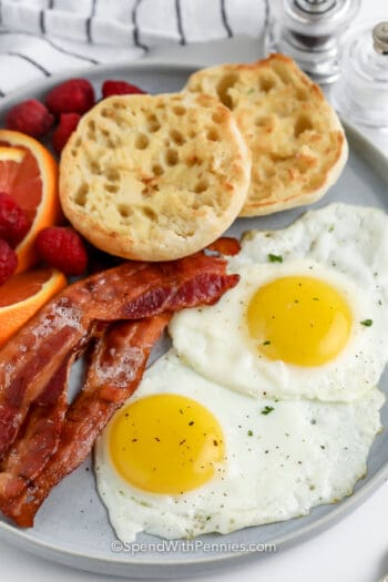 two fried eggs on plate with english muffin, bacon, and fruit