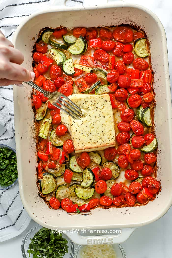 mixing baked feta with roasted vegetables
