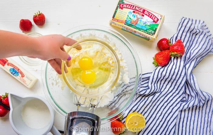 adding egg to bowl to make Strawberry Bread