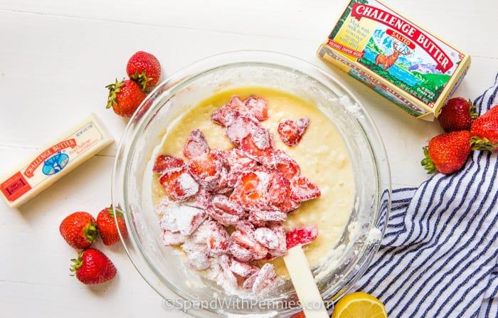 adding strawberries to bowl to make Strawberry Bread