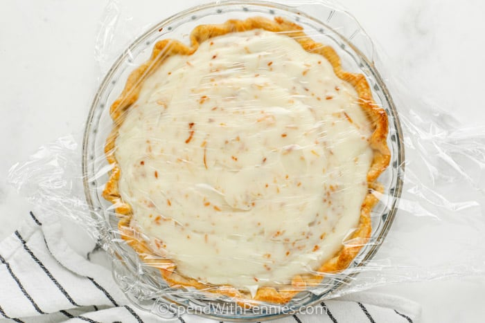 Ultimate Coconut Cream Pie with plastic wrap over top