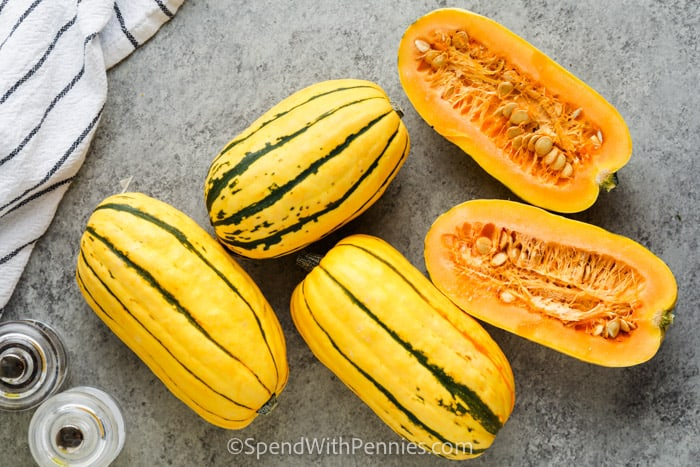 full squash on a table and one cut in half to show What is Delicata Squash