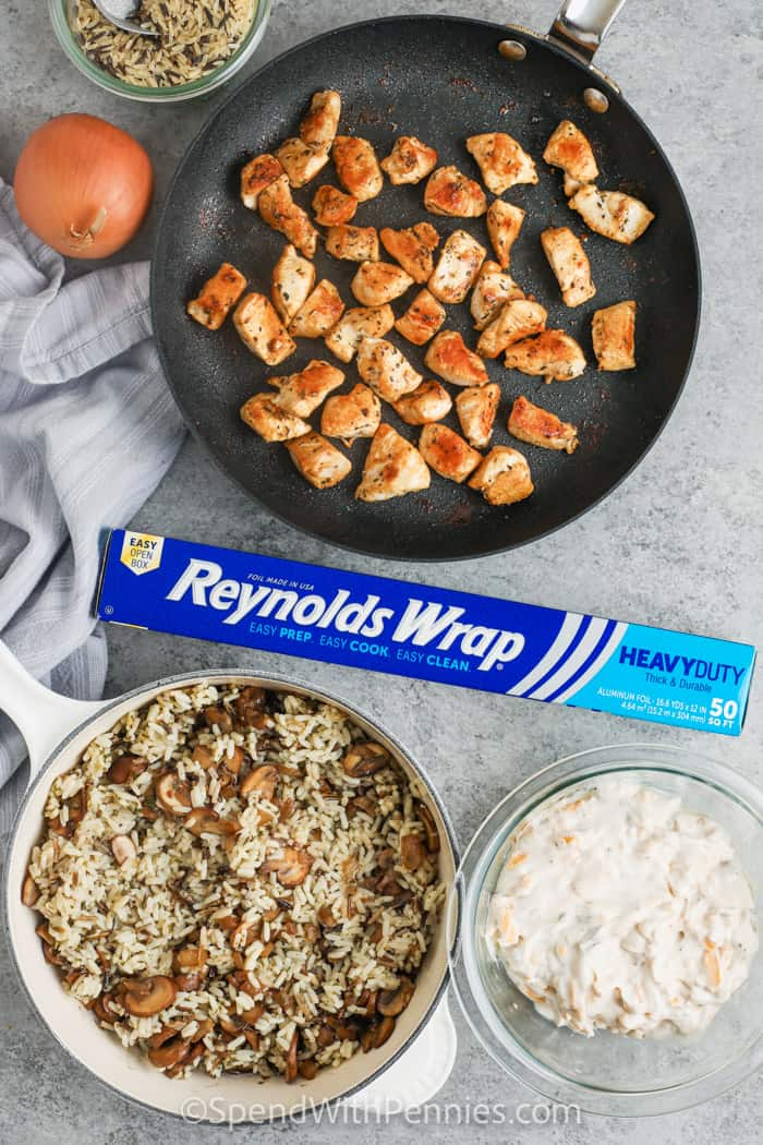 cooking chicken with other ingredients in bowls mixed and Reynolds wrap to make Chicken and Wild Rice Casserole