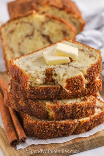 Cinnamon Bread in a stack with butter on top and a bite taken out