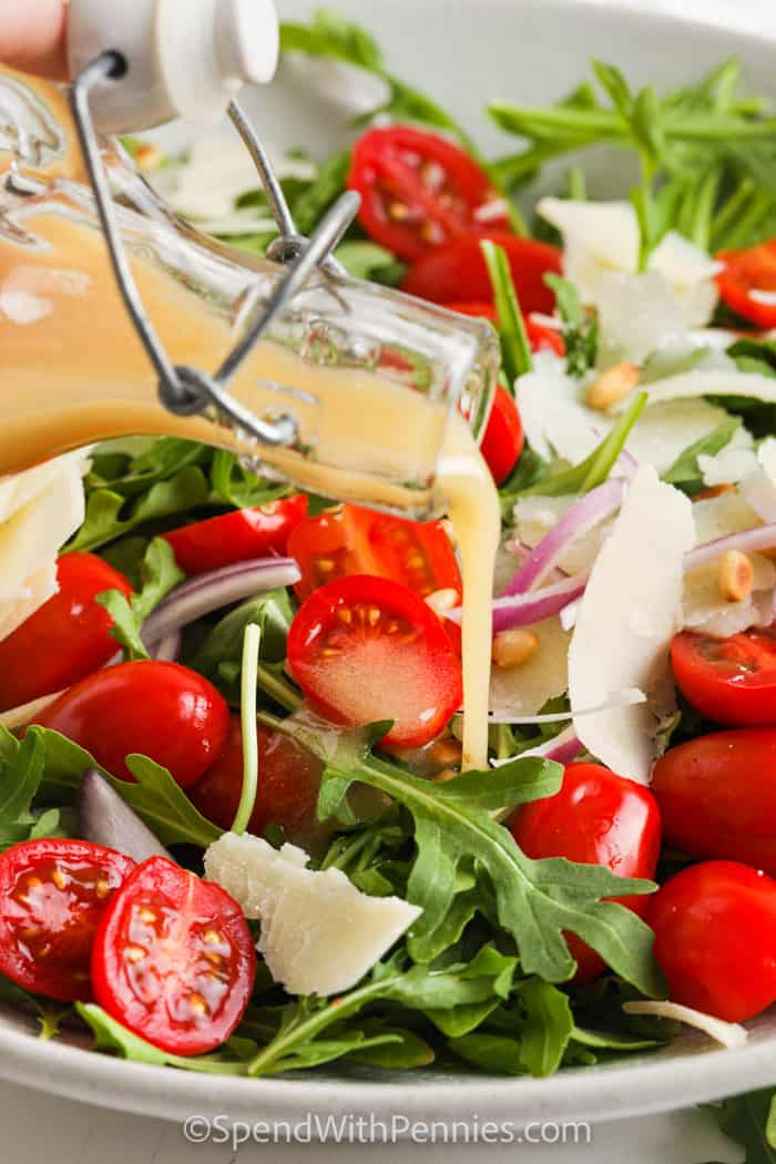 pouring dressing over Easy Arugula Salad
