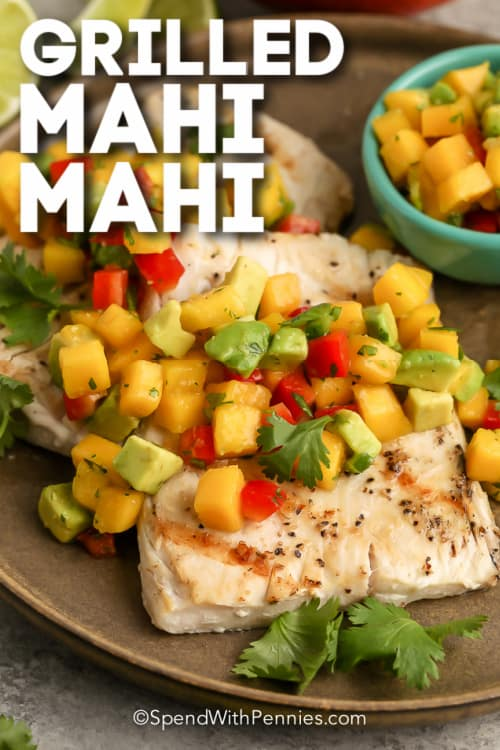 Grilled Mahi Mahi topped with mango salsa on a brown plate with text