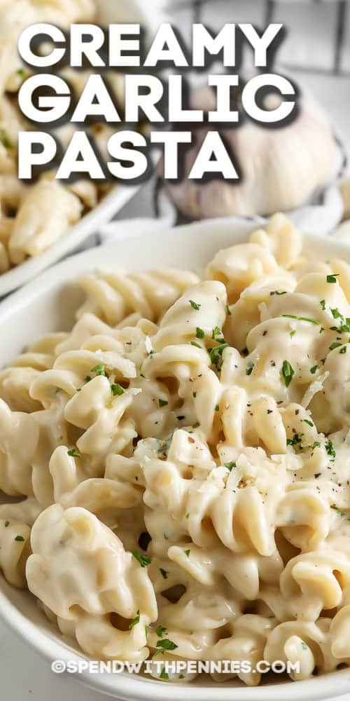 creamy garlic pasta in a white bowl with text