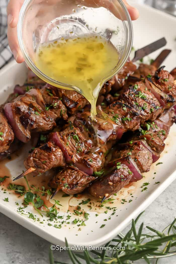 pouring garlic sauce over cooked steak kabobs