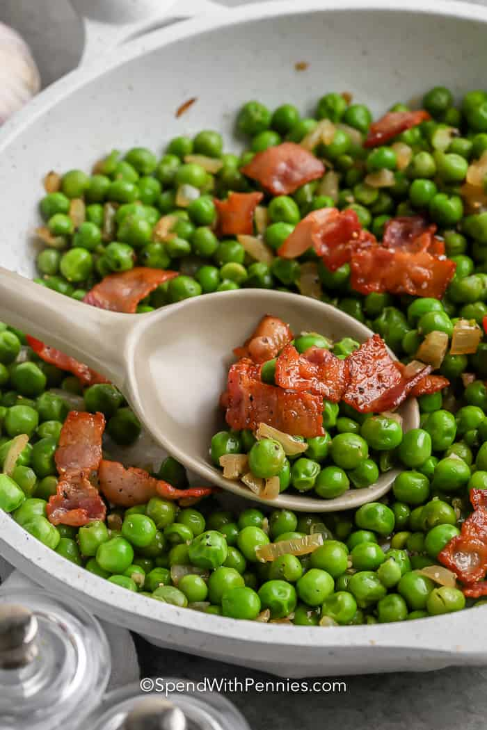 spoon scooping Green Peas with Bacon