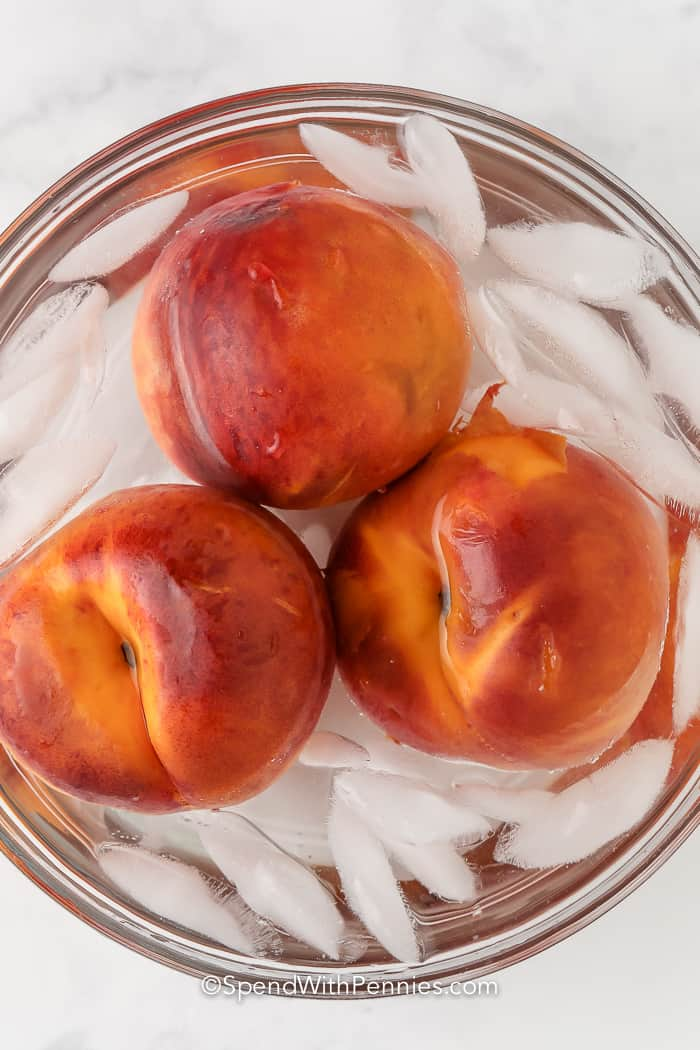 three peaches in a bowl with ice