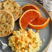 scrambled eggs on a plate with english muffins and orange wedges