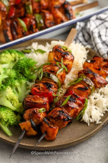 teriyaki chicken kabobs on a bed of rice with steamed broccoli