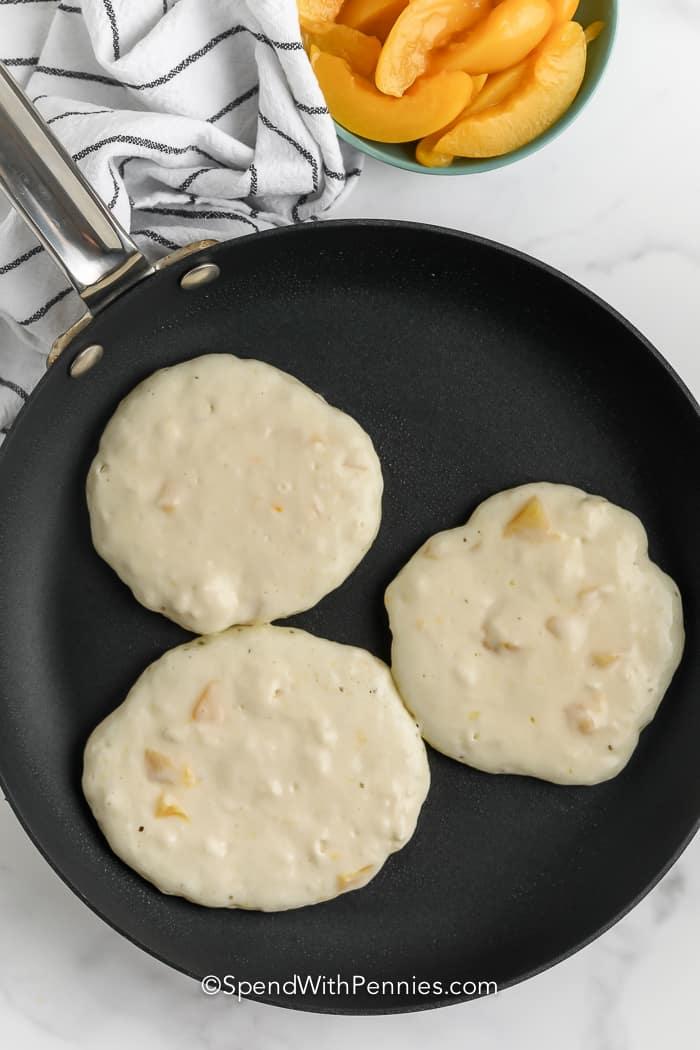 three yogurt pancakes cooking on a frying pan