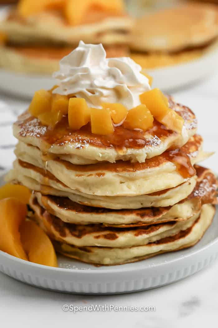 stack of yogurt pancakes topped with peaches and whipped cream