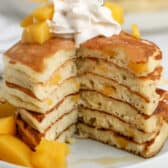 stack of yogurt pancakes topped with peaches with slice taken out