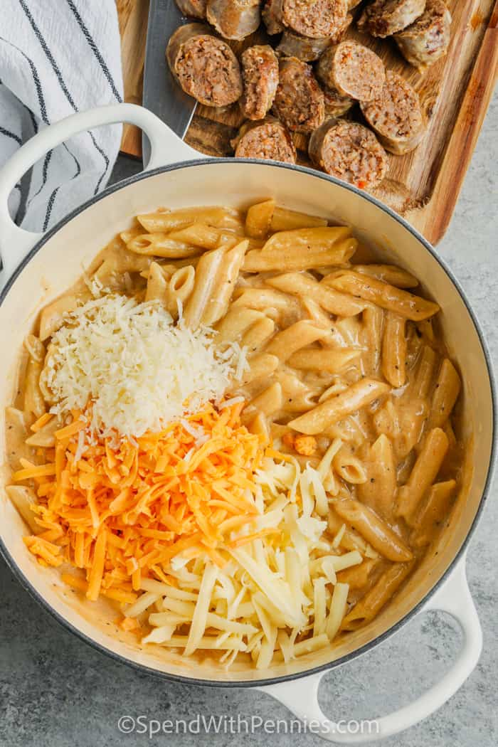 adding cheese to pot to make Stove Top 3 Cheese Pasta with Sausage
