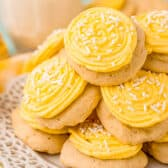 pile of lemon cookies with yellow icing and white sprinkles on a plate