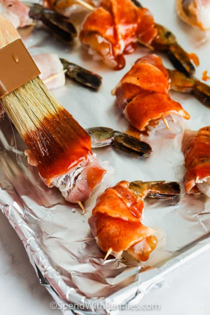 brushing sauce over Bacon Wrapped Shrimp