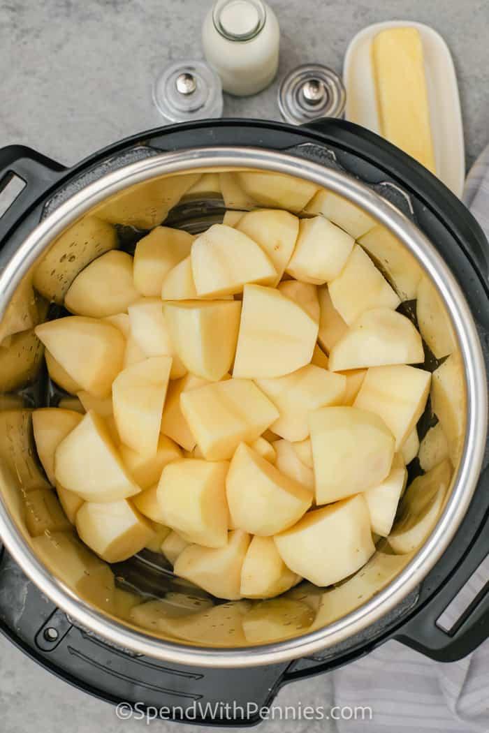 adding potatoes to pot to make Instant Pot Mashed Potatoes