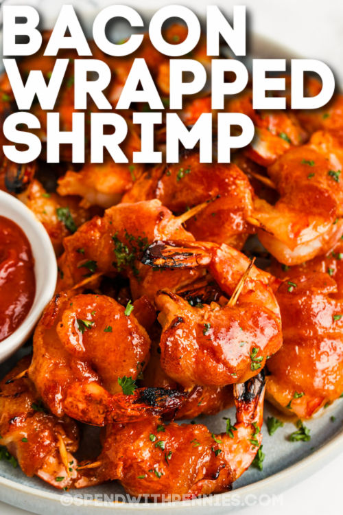 cooked Bacon Wrapped Shrimp on a plate with writing