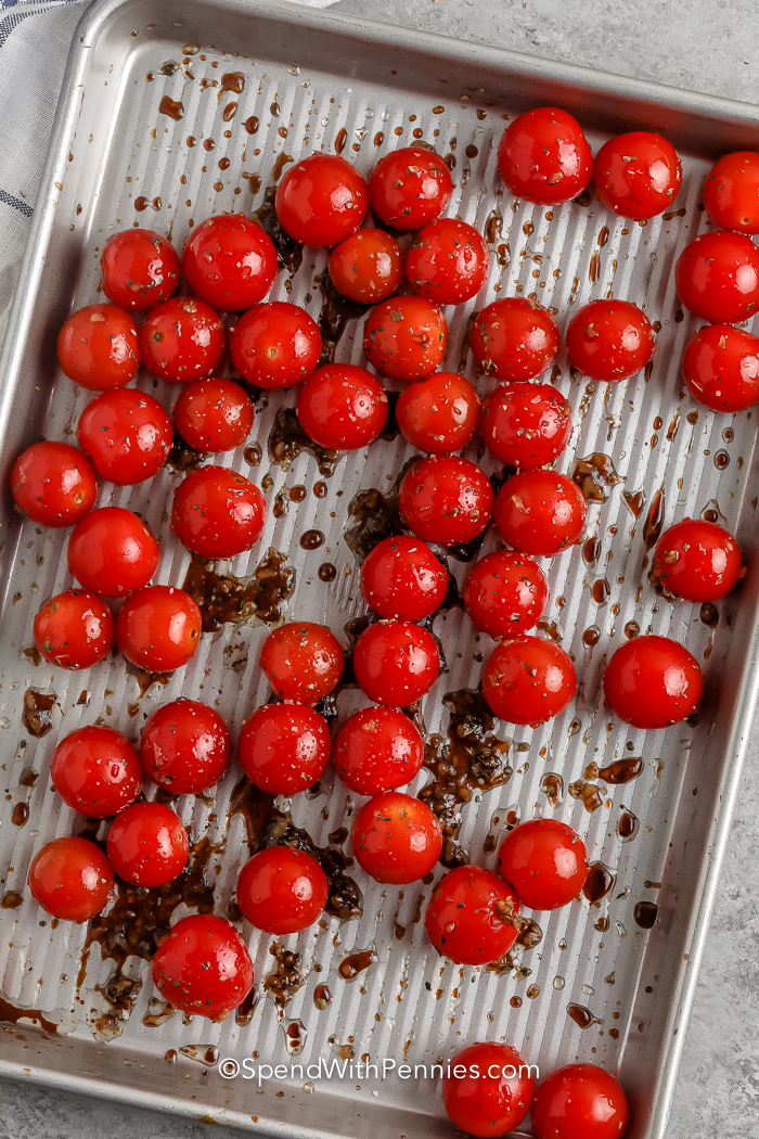 cherry tomatoes on a pan tossed in balsamic vinegar and garlic