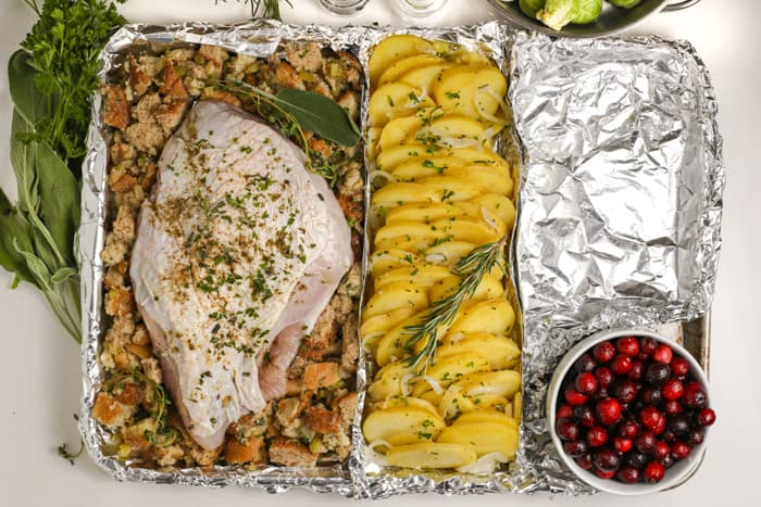 uncooked turkey breast and potatoes on a sheet pan