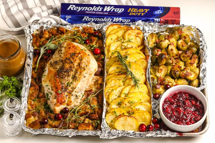 turkey dinner on a sheet pan with a bowl of cranberry sauce