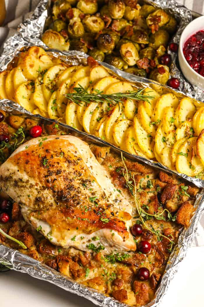 a turkey dinner on a sheet pan topped with fresh herbs