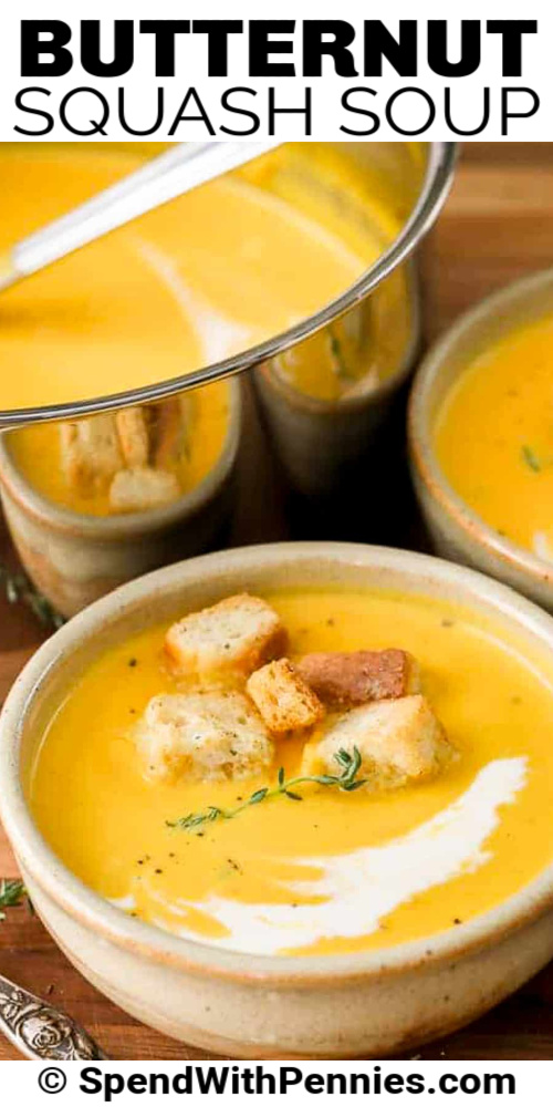 A bowl of butternut squash soup with a pot behind it with writing