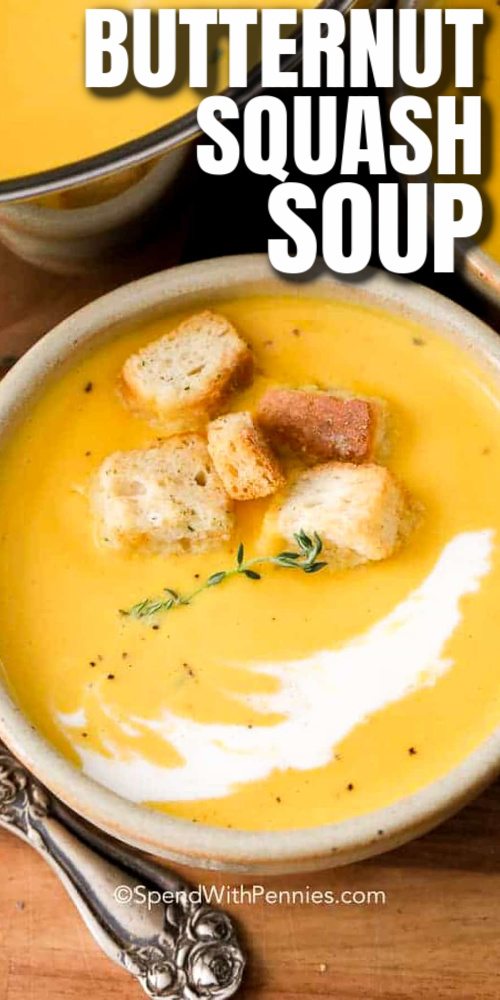 A serving of butternut squash soup topped with croutons with writing