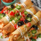 Jalapeno Air Fryer Taquitos on a white plate with garnish